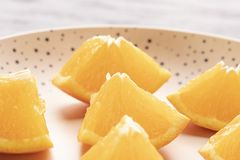 Freshly sliced oranges on a dotted brown plate royalty free stock photo