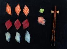 Freshly sliced sushi on natural slate stone background. Overhead view of fresh Japanese sushi, ginger, wasabi, and chopsticks on black slate Stock Images