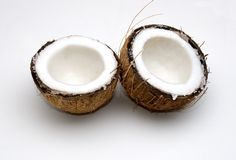 A Freshly Split Coconut. Two halves of a freshly split and drained coconut, showing the soft, white coconut meat inside the shell stock images