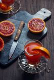 Freshly Squeezed Blood Orange Juice with Oranges. A glass of freshly squeezed Sicilian blood orange juice on a table next to a gray stone cutting board. A knife Stock Image