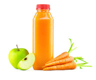 Freshly Squeezed Carrot Apple Juice in Bottle. A generic bottle of freshly squeezed raw carrot and apple juice with a garnish of carrots and apples on the side Stock Image