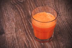 Freshly squeezed carrot juice in glass. Freshly squeezed orange carrot juice in glass Stock Images