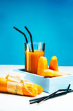 Freshly squeezed carrot juice in the glasses. A box with purified carrot on a blue wooden background Stock Photo