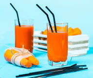 Freshly squeezed carrot juice in the glasses. A box with purified carrot on a blue wooden background Royalty Free Stock Images