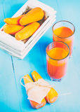 Freshly squeezed carrot juice in the glasses. A box with purified carrot on a blue wooden background Royalty Free Stock Image