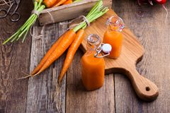 Freshly squeezed carrot juice and organic raw vegetables. Over rustic wooden table, harvest time Stock Photos