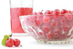 Freshly squeezed cherries juice. Glass of freshly squeezed juice, dish full of Far-East cherries and two cherries with green leaf isolated on white background Stock Images