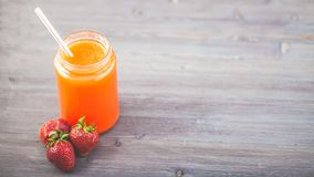 Freshly squeezed fruit juice, smoothies orange orange strawberry on a dark wooden background Copy space.  stock photos
