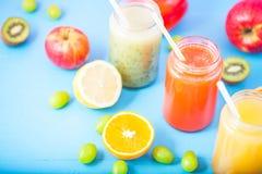 Freshly squeezed fruit juice, smoothies yellow orange green blue banana lemon apple orange kiwi grape strawberry on blue backgroun. D Copy space Flat lay stock images