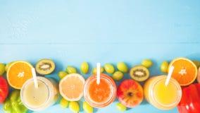 Freshly squeezed fruit juice, smoothies yellow orange green blue banana lemon apple orange kiwi grape strawberry on blue backgroun. D Copy space. Flat lay Banner stock image