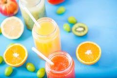 Freshly squeezed fruit juice, smoothies yellow orange green blue banana lemon apple orange kiwi grape strawberry on bright blue ba. Ckground Copy space stock images
