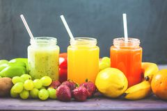 Freshly squeezed fruit juice, smoothies yellow orange green blue banana lemon apple orange kiwi grape strawberry on a dark wooden. Background Copy space stock images