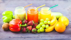 Freshly squeezed fruit juice, smoothies yellow orange green blue banana lemon apple orange kiwi grape strawberry on a dark wooden. Background Copy space stock photo