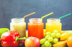 Freshly squeezed fruit juice, smoothies yellow orange green blue banana lemon apple orange kiwi grape strawberry on a dark wooden. Background Copy space royalty free stock photos