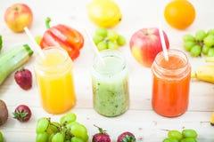 Freshly squeezed fruit juice, smoothies yellow orange green blue banana lemon apple orange kiwi grape strawberry on a light wooden. Background Close up royalty free stock photography