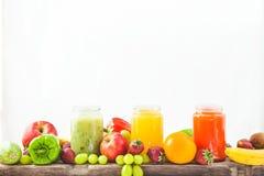Freshly squeezed fruit juice, smoothies yellow orange green blue banana lemon apple orange kiwi grape strawberry on a white isolat. E background royalty free stock photo