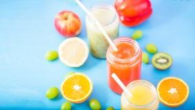 Freshly squeezed fruit juice, smoothies yellow orange green blue banana lemon apple orange kiwi grape strawberry on blue backgroun. D Copy space Flat lay royalty free stock photos