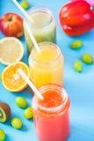 Freshly squeezed fruit juice, smoothies yellow orange green blue banana lemon apple orange kiwi grape strawberry on bright blue ba. Ckground Close up stock photography