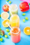 Freshly squeezed fruit juice, smoothies yellow orange green blue banana lemon apple orange kiwi grape strawberry on bright blue ba. Ckground Close up royalty free stock images
