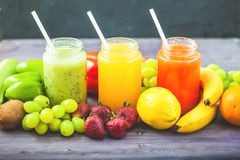 Freshly squeezed fruit juice, smoothies yellow orange green blue banana lemon apple orange kiwi grape strawberry on a dark wooden. Background Copy space stock photos