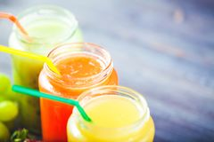 Freshly squeezed fruit juice, smoothies yellow orange green blue banana lemon apple orange kiwi grape strawberry on a dark wooden. Background Copy space royalty free stock image