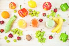 Freshly squeezed fruit juice, smoothies yellow orange green blue banana lemon apple orange kiwi grape strawberry on a light wooden. Background Close up Flat lay stock image