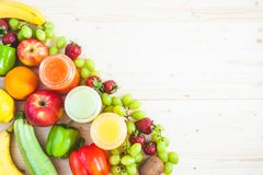 Freshly squeezed fruit juice, smoothies yellow orange green blue banana lemon apple orange kiwi grape strawberry on a light wooden. Background Copy space Flat stock image