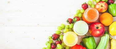 Freshly squeezed fruit juice, smoothies yellow orange green blue banana lemon apple orange kiwi grape strawberry on a light wooden stock photo