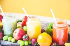 Freshly squeezed fruit juice, smoothies yellow orange green blue banana lemon apple orange kiwi grape strawberry on a yellow backg. Round stock images