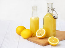 Freshly squeezed lemon juice in bottle and lemons on light background. For vitamin drink or cocktail. Stock Images