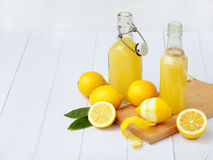 Freshly squeezed lemon juice in bottle and lemons on light background. For vitamin drink or cocktail. Royalty Free Stock Photo