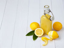 Freshly squeezed lemon juice in bottle and lemons on light background. For vitamin drink or cocktail. Royalty Free Stock Photos