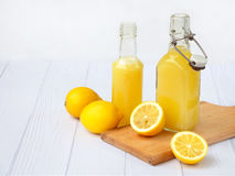 Freshly squeezed lemon juice in bottle and lemons on light background. For vitamin drink or cocktail. Selective focus. Royalty Free Stock Photos