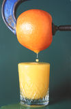 Freshly Squeezed Orange. Orange being squeezed to create juice Stock Photo