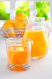 Freshly squeezed orange juice for breakfast. Standing on a white tabletop with a full glass tumbler and jug and a bowl of fresh oranges in the background Royalty Free Stock Photography