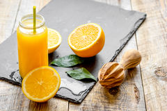 Freshly squeezed orange juice in glass bottle on wooden background Stock Photo