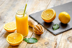 Freshly squeezed orange juice in glass bottle on wooden background Royalty Free Stock Image