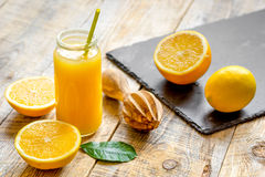 Freshly squeezed orange juice in glass bottle on wooden background Royalty Free Stock Images