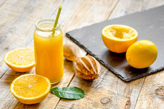 Freshly squeezed orange juice in glass bottle on wooden background Stock Photography