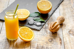 Freshly squeezed orange juice in glass bottle on wooden background Stock Images