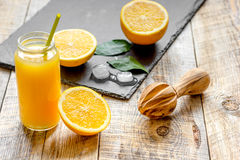 Freshly squeezed orange juice in glass bottle on wooden background Royalty Free Stock Photos