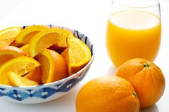 Freshly squeezed orange juice in a glass next to a bowl of orange slices and two oranges just picked off the tree on a white table royalty free stock images
