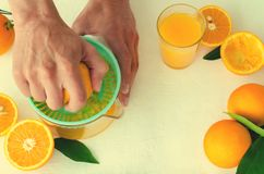 Freshly squeezed orange juice by men`s hands, in turquoise juicer on white background Royalty Free Stock Image