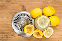 Freshly squeezed organic lemon juice with glass and squeezer. Royalty Free Stock Photos