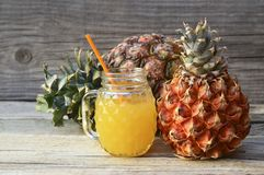 Freshly squeezed pineapple juice in a glass cup with drinking straw and ripe ananas fruits on old wooden table. Healthy food,diet or vegan food concept stock photography