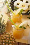 Freshly squeezed pineapple juice in a glass jar closeup. vertica Royalty Free Stock Photography