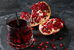 A freshly squeezed pomegranate drink with a black straw on a dark gray background. The ripe and organic red garnet cut Stock Images