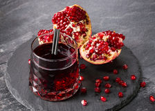 A freshly squeezed pomegranate drink with a black straw on a dark gray background. The ripe and organic red garnet cut Royalty Free Stock Image