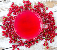 Freshly squeezed red juice, and bunches of red currants on a white wooden table with old paint Stock Photo