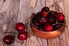 Freshly washed cherries in wooden bowl royalty free stock photos